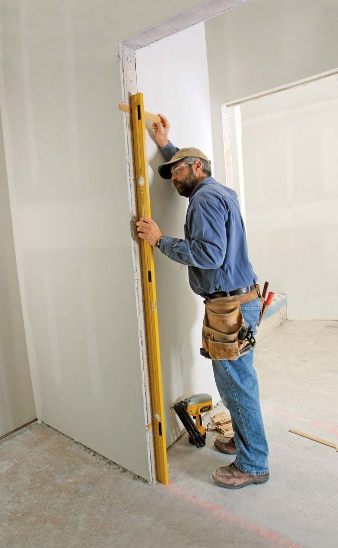 Plumb the opening with one shim at each hinge location indicated by the black tape on a door-hanging level.