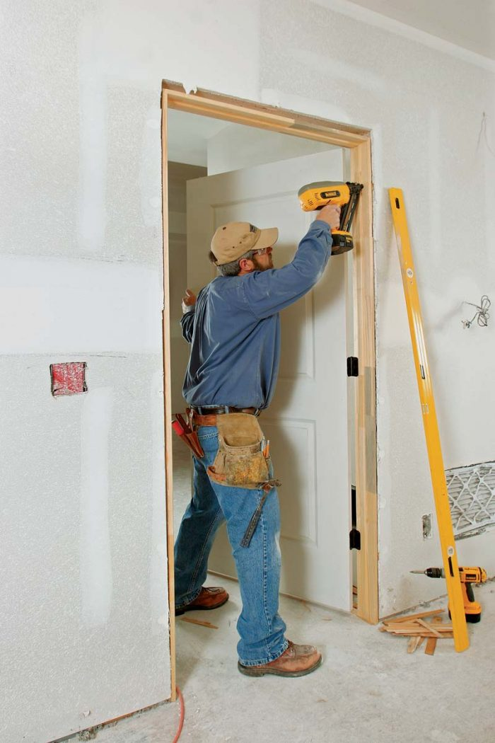 Start by nailing the hinge side in place. Then shim and nail the latch side to create an even reveal (or space) between the door and the jamb, about the thickness of a nickel.