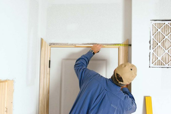 Tip the door in place; then center it by measuring the space between the drywall and the casing.