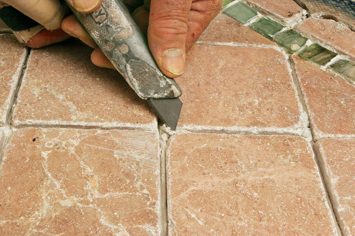 Use a utility knife or the edge of a margin trowel to remove any hardened chunks of thinset from the tile.