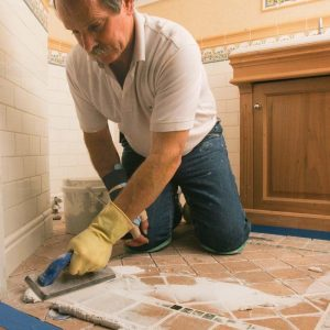 Use the margin trowel to scoop a small pile of epoxy grout onto the floor, and begin spreading it across the tile,