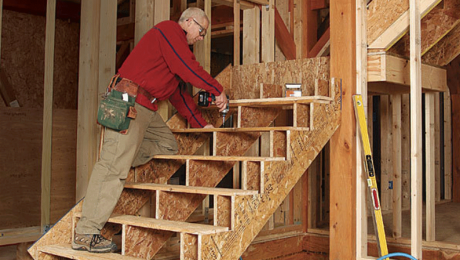 man building a staircase with a landing