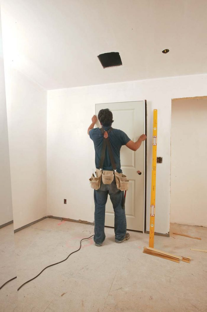 Alex has a 6-ft. level, and he stands on the interior of the door to establish a plumb hinge side and to check the gap around the door.