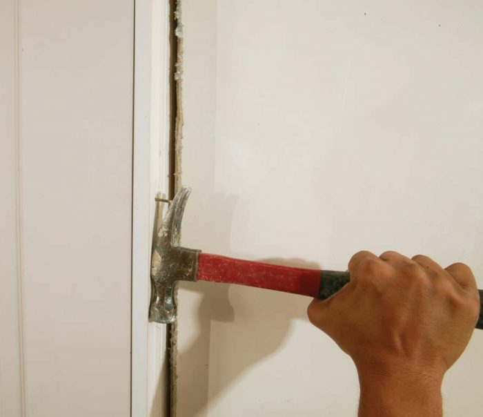 Remove the nail holding the door to the jamb and any cardboard shims stapled to the edge of the door.