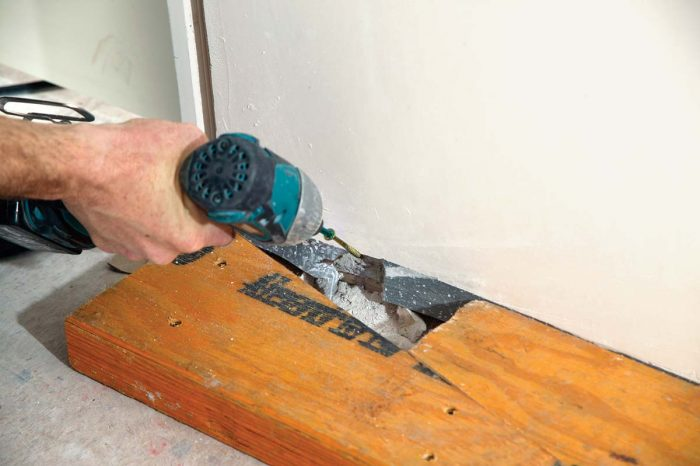 Cut two wedges from heavy stock, and screw one to the floor near the wall.