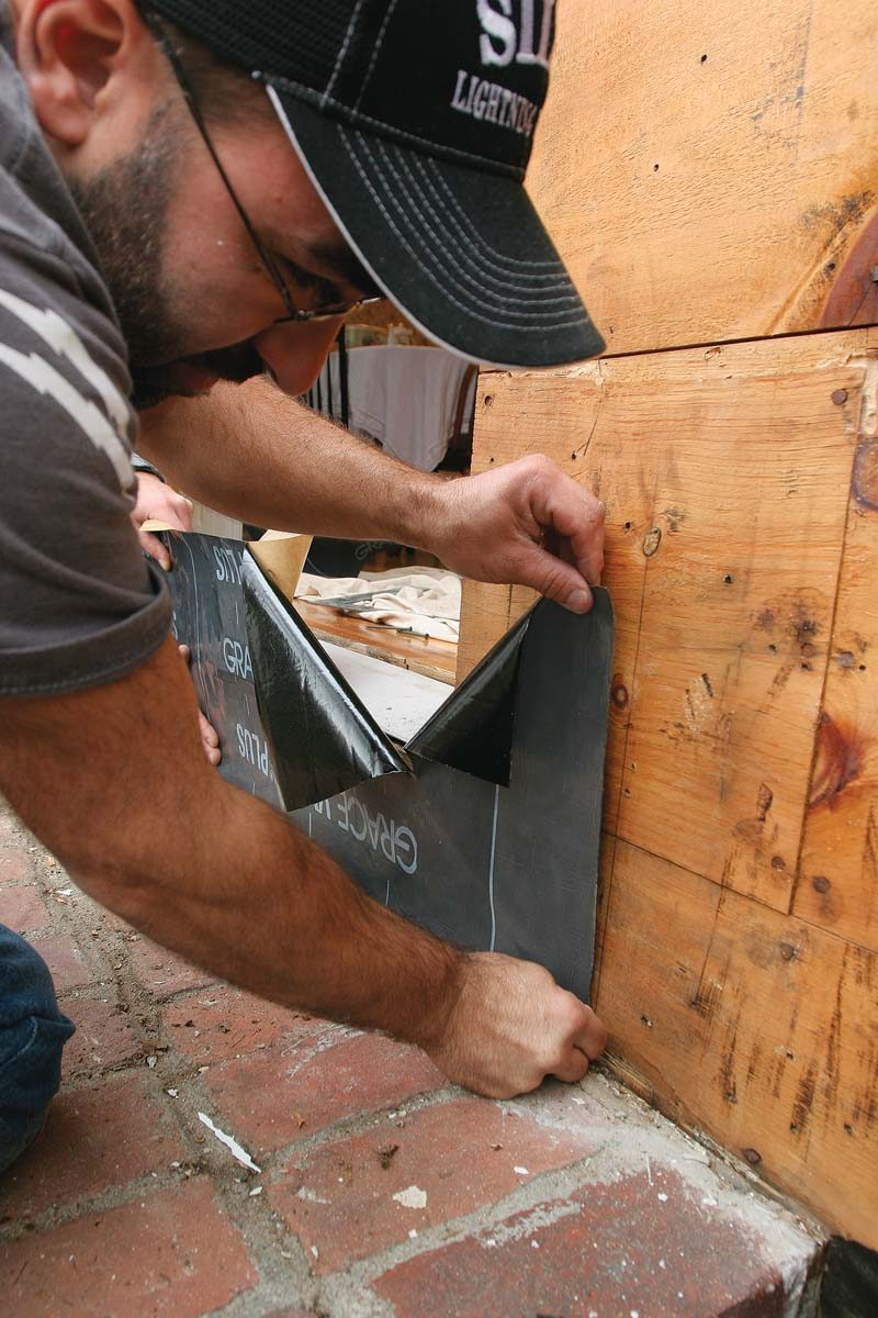 Held to a plumb line on the sheathing, the first piece of flashing extends across the bottom of the opening.