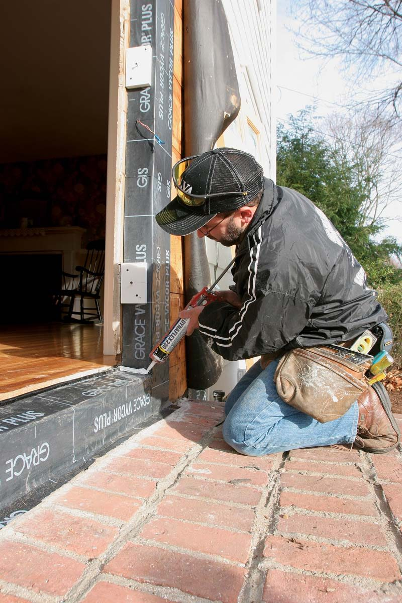 A rolled-up piece of flexible flashing keeps water and air from seeping between the bottom of the threshold and the sill.