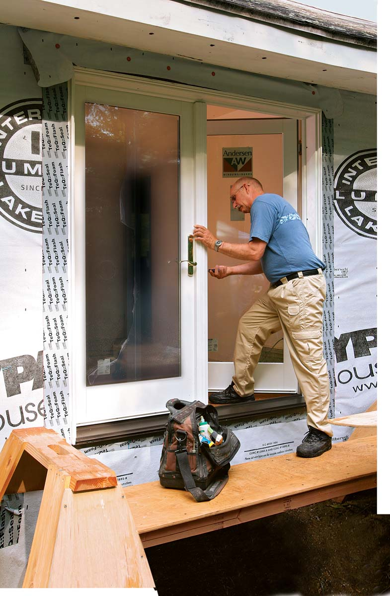 Once the door operates easily and is fully fastened, tape over the door's installation flange with flexible flashing, and install the hardware.