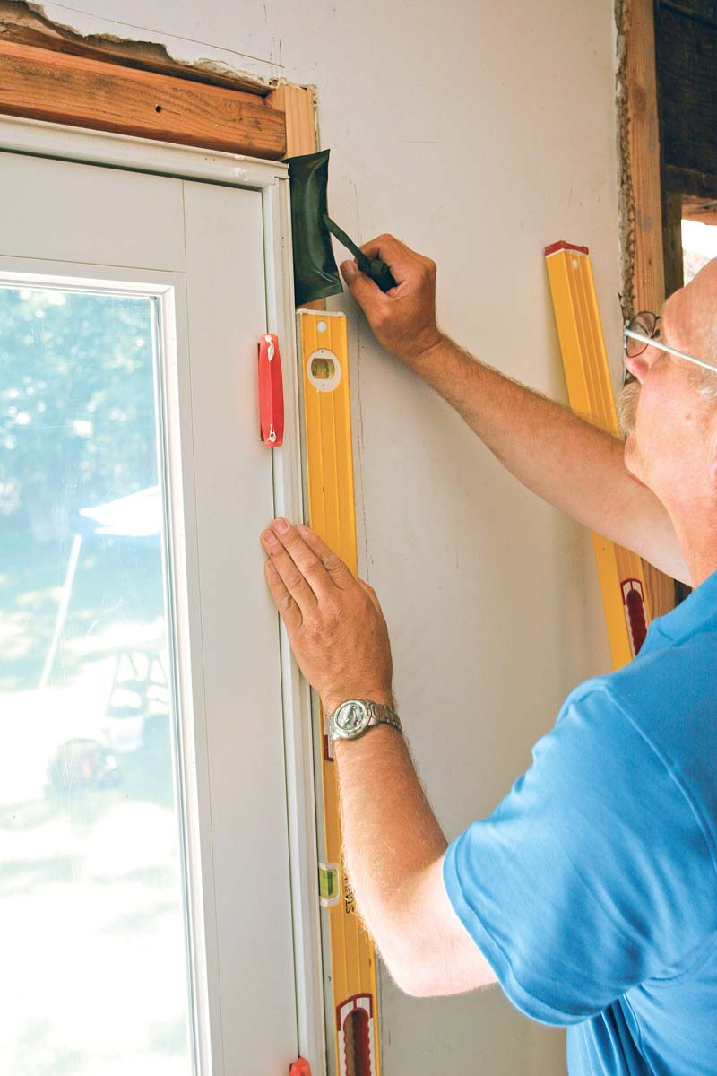 With the help of a 6-ft. level, the author matches the door to the wall's out-of-plumb condition as best he can without sacrificing the door's operation.