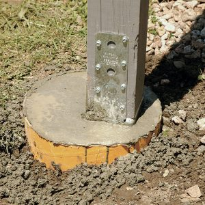 Offset for a reason. With the concrete in place, it's apparent that the post is not centered. The author offset the footing to make room for an additional post to support a new rim beam.