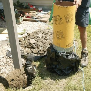 A better footing. After removing the old footings, dig the holes deeper and wider. Based on the footing-size table in DCA-6, footings need to be 16 in. dia. Local code specifies a 40-in. depth. On this job, the author used 12-in.-dia. form tubes with garbage bags taped to the bottom. The bags contain the concrete while permitting it to fill the 16-in.-dia. base entirely at the bottom of the hole. The bags also isolate the concrete from groundwater and soil contamination.