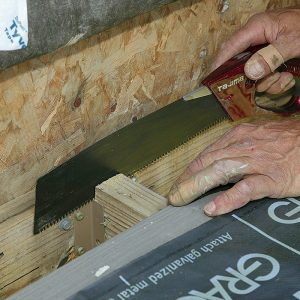 Prepare for framing. Remove the door riser board, the siding, and the first deck board to inspect for rot. After folding up the housewrap, cut a shallow kerf in the joist tops for the flashing edge.