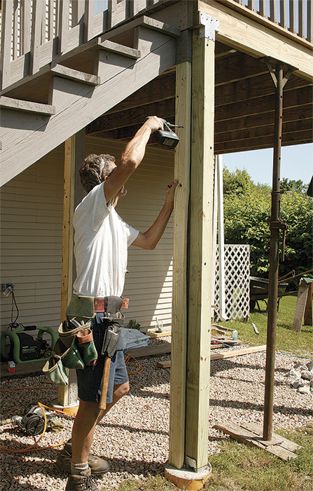 The header needs support. Position 2x4 pressure-treated jacks from the footings to beneath each end of the stringer header, and attach them to the 4x4 posts with structural screws.