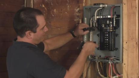 man installing circuit breaker