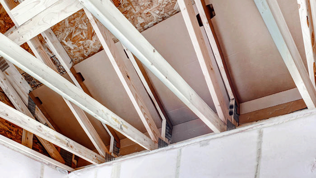 A 14-in. increase in the height of roof trusses leaves more space for insulation at the eaves. A full R-50 of blown-in fiberglass blankets the floor of the vented attic. Netting is stapled to the face of inside studs creating a 9 1/2-in.-deep wall cavity for insulation.