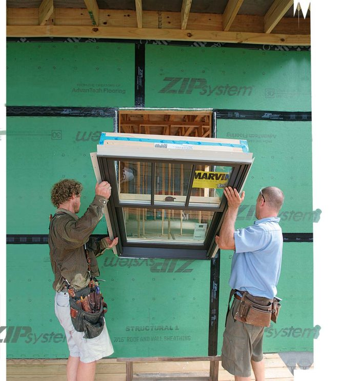 est the window on the edge of the sill, tip it upright, and slide it straight in against the caulked sheathing.