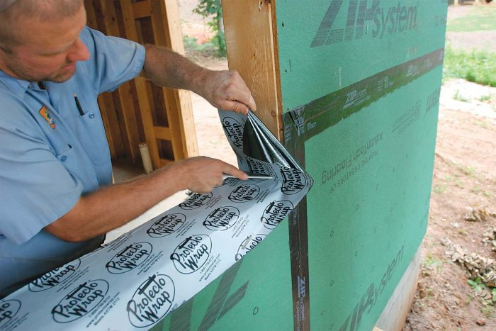 Use a rafter square to press the tape tightly into the corners where the sill meets the sides of the rough opening,