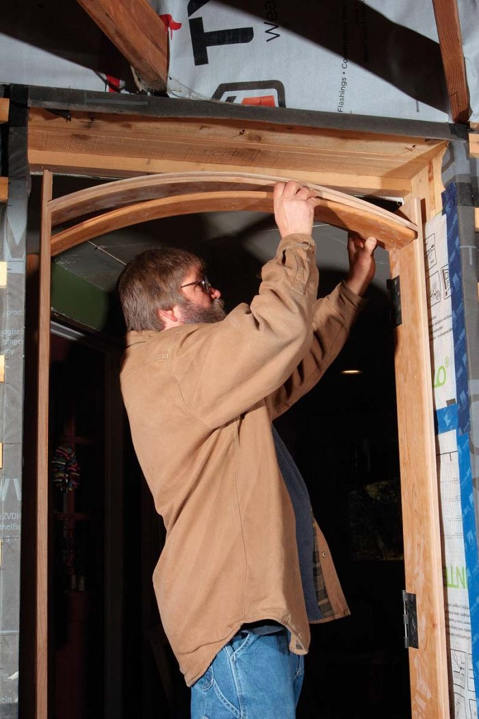 Fasten the jambs and install the stop. Once the side jambs are plumb and securely fastened with structural screws, the first layer of the two-layer stop is fastened to the head jamb with 1-in. screws.