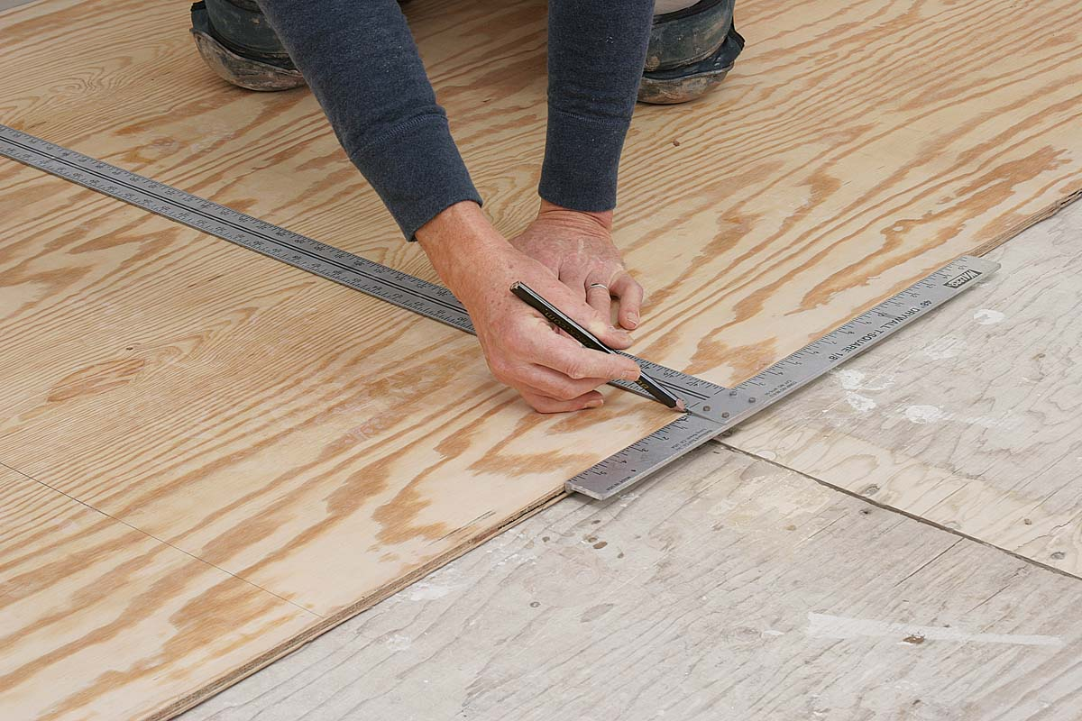 Run the underlayment perpendicular to the joists, making sure its ends and edges miss the joists and seams in the subfloor by at least 2 in.