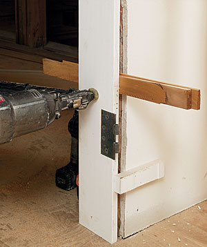 drive a screw through the shim. Small blocks tacked to the drywall register the jamb's hinge side to the drywall's face.