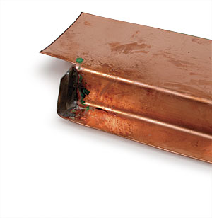 Press a hot iron into the corner to heat the copper and the flux.