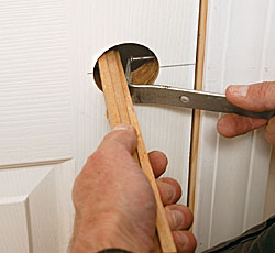 Use a nail to mark the center of the strikeplate hole