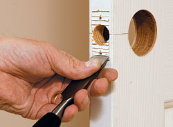 Hold a sharp chisel at about a 45° angle to the work, and score the face of the mortise by gently tapping the chisel with a hammer