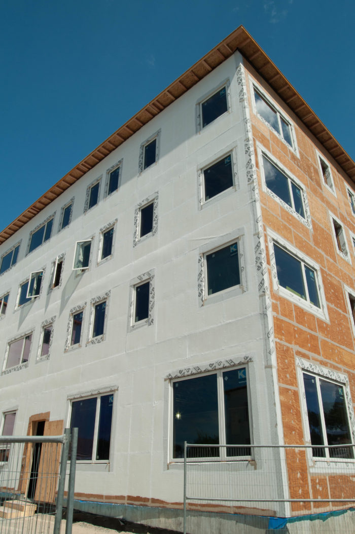 Air-sealing is crucial if the building is to win PHIUS+ 2015 certification. Designers chose a fluid-applied air barrier, seen here as the white coating on the left side of the building. The plywood sheathing on the right has yet to be sealed.