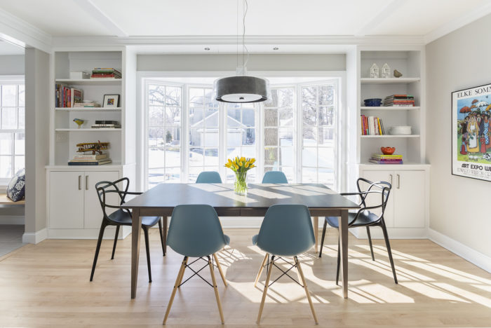 Bright sunny kitchen table with bay window and modern table and chairs