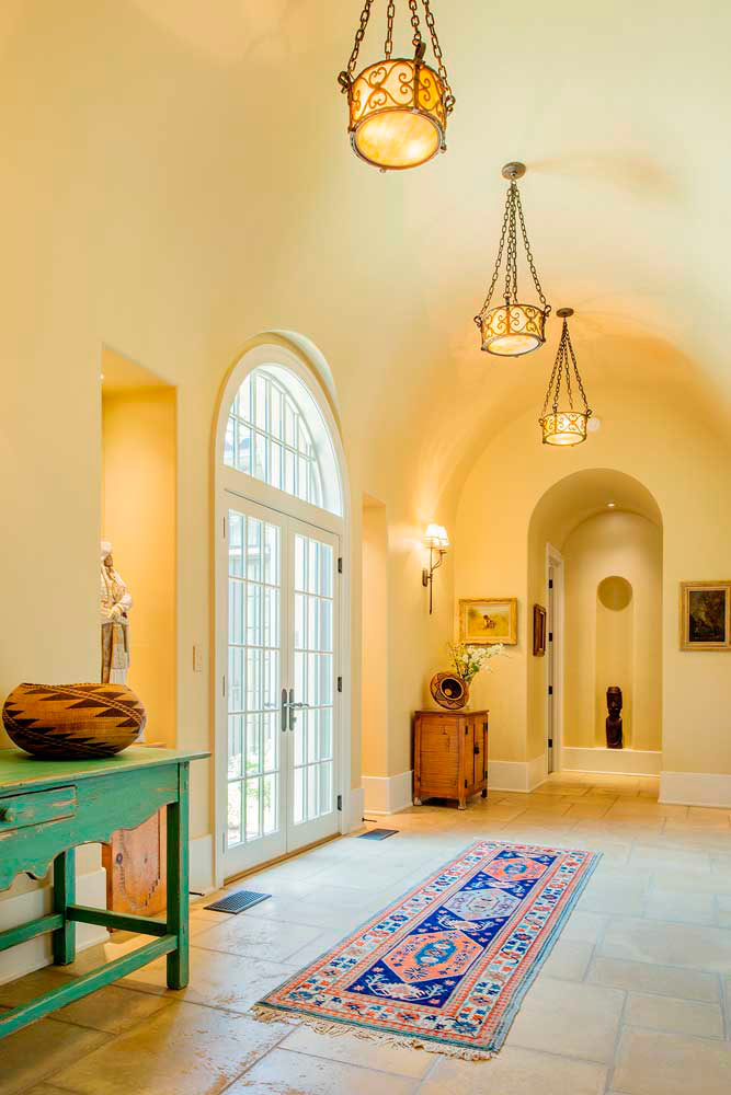 French inswing doors crowned by a round top window splash natural light across this arched hallway.