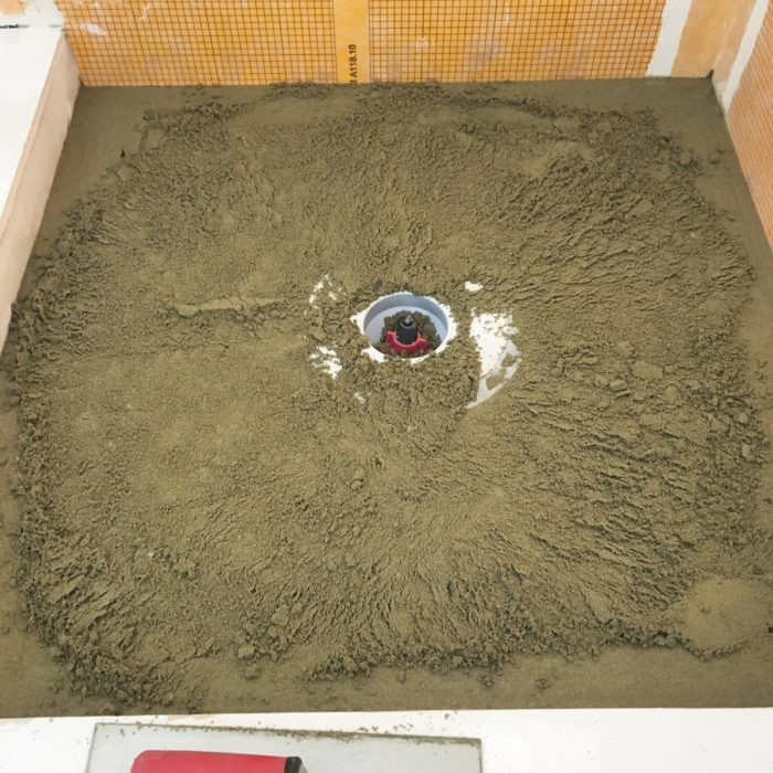 start screeding the inside area of the pan using your perimeter screeds and the drain as a gauge to how much mortar needs to be removed