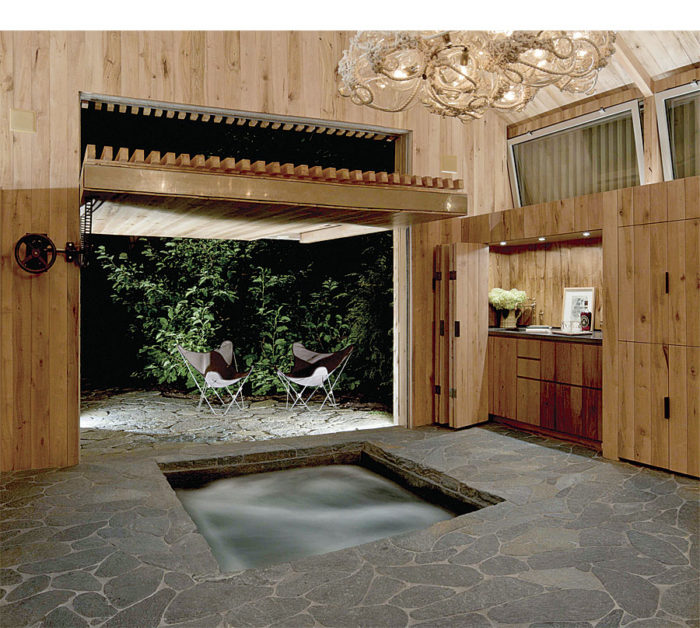 A 10-ft. by 10-ft. counterbalance door lifts up and outward to connect the interior and exterior. The millwork is reclaimed chestnut, and the flooring is galaxy schist from a local quarry. The water in the hot tub is treated with natural enzymes, allowing it to be collected along with rainwater in a cistern and then used to water the lawn and gardens.