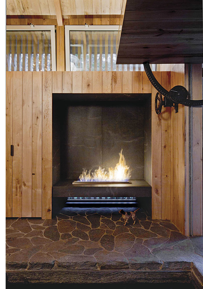 The custom EcoSmart Fire fireplace burns ethanol. The interior walls are reclaimed maple floor planks. The cantilevered door is manually operated by a large wheel and gear.