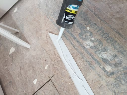 Apply a bead of paintable adhesive caulk to the back side of the molding pieces.