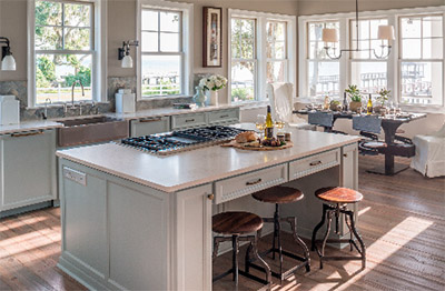 An open concept together with a neutral color palette reflect the serene natural setting highlighted through the kitchen's wall of windows. Open concept design and airy features make this kitchen ideal for both entertaining and easy island living.