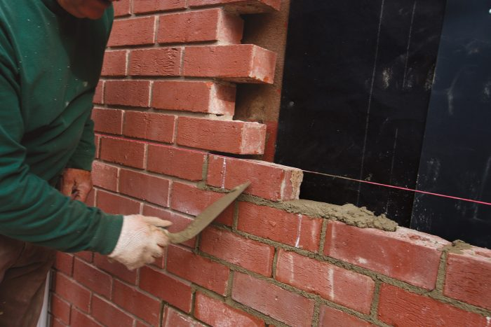 cutting off the excess mortar