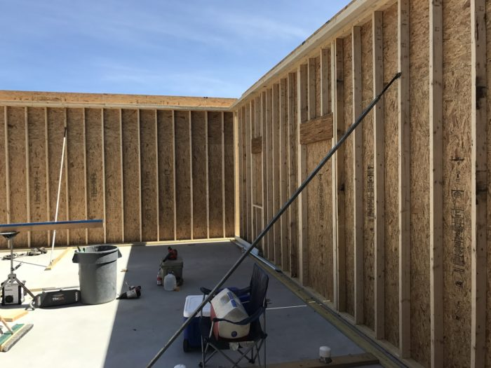 Exterior 2x4 wall framed and lifted with 2x12 top plate attached.