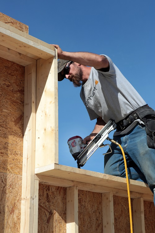 Mike nails off the top plate to accept the interior studs of the double-stud wall.