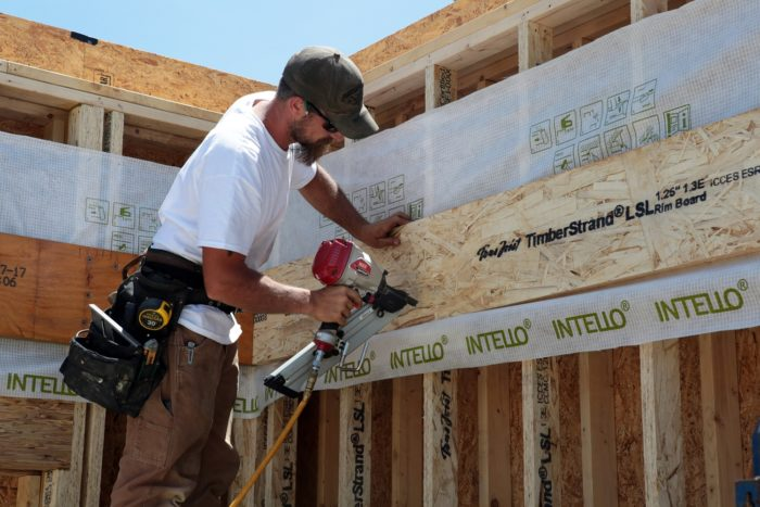 A splice of Intello is tacked in place before Mike uses the MAX framing nailer to hang the rim board for the second floor system. The strip of membrane ensures a continuous air barrier after framing is complete.