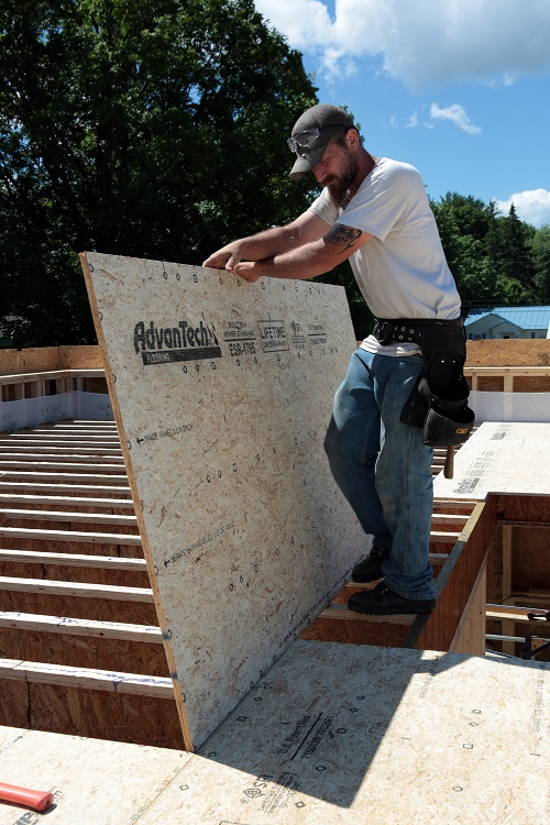 With the adhesive applied to the top of the joists, an AdvanTech flooring panel is moved into place. The adhesive sets up pretty quickly so don't apply it too far ahead of where you're working.