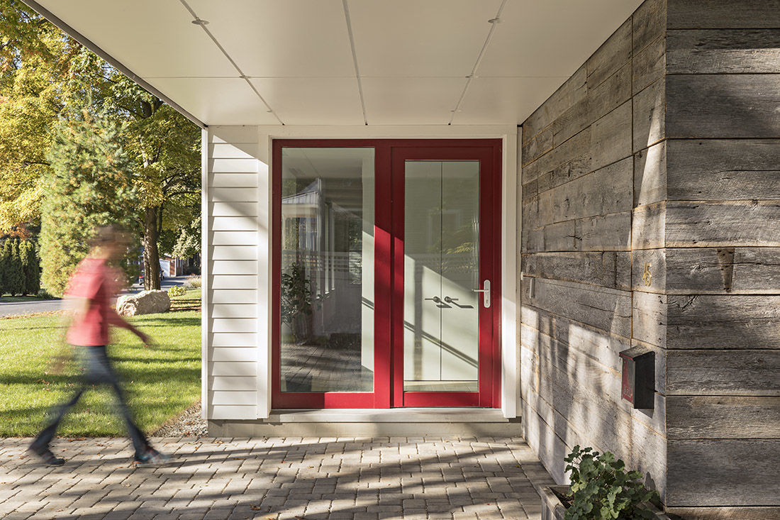 turning the front entrance to the side and tucking it under the second floor overhang allowed the architects to include a big glass door without making it - New Home Architecture