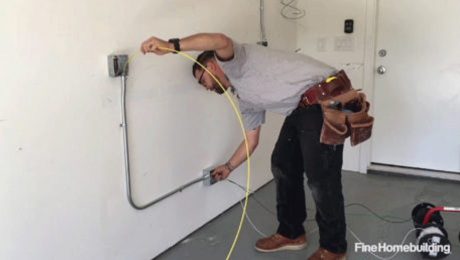 person working on wiring conduit