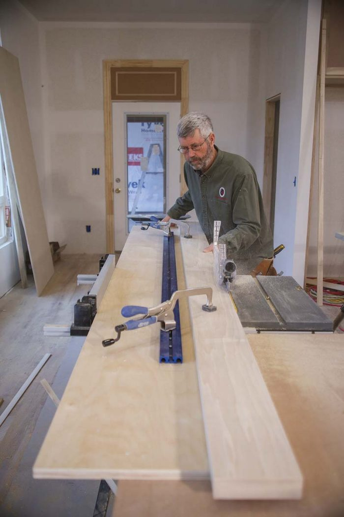 To put a straight edge on a board on the job site, make a long plywood sled, clamp the board on it, and run the sled against the tablesaw fence, making sure the blade is set accurately to 90°.