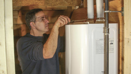 This tankless water heater has hose clamps for connecting the combustion-air and flue-gas piping to the top of the water heater.