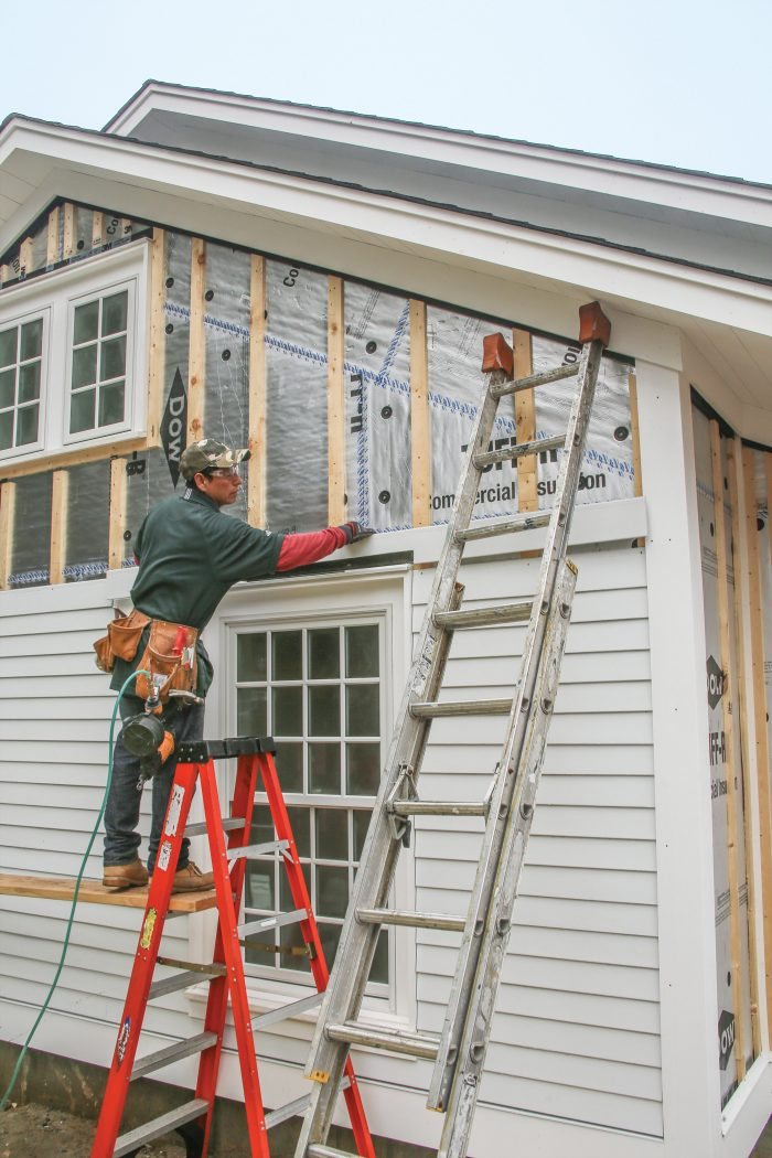 The flat casing surrounding each window and door is topped with a PVC drip cap and an aluminum drip cap.