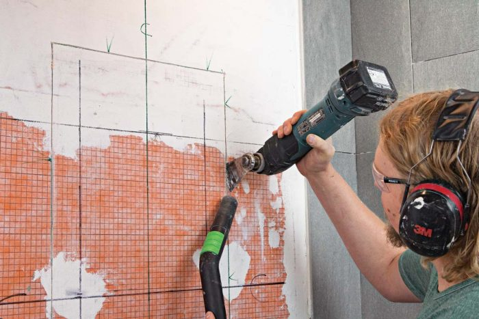 An oscillating multitool makes short work of wallboard cuts, and a vac hose tames the dust.
