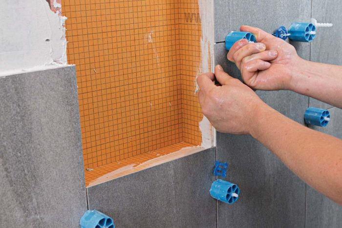 To ensure even grout lines, perfectly flush tiles, and tight joints, cut and miter carefully, apply the right amount of thinset, and use a tile-leveling system.