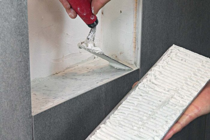 All tile—wall and niche—gets thinset on its back side and a layer where it will sit to ensure a good bond.