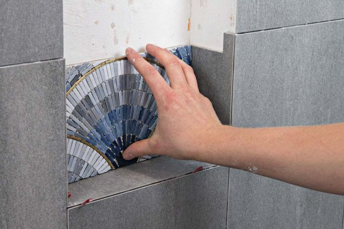 Cut the lower back tiles—in this case a mosaic of glass—to fit with an even gap at either side and along the bottom.