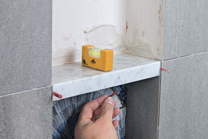 The shelf needs the same subtle downward slope as the bottom of the niche, and wedge spacers ensure thin, even grout lines at the side and bottom edges.
